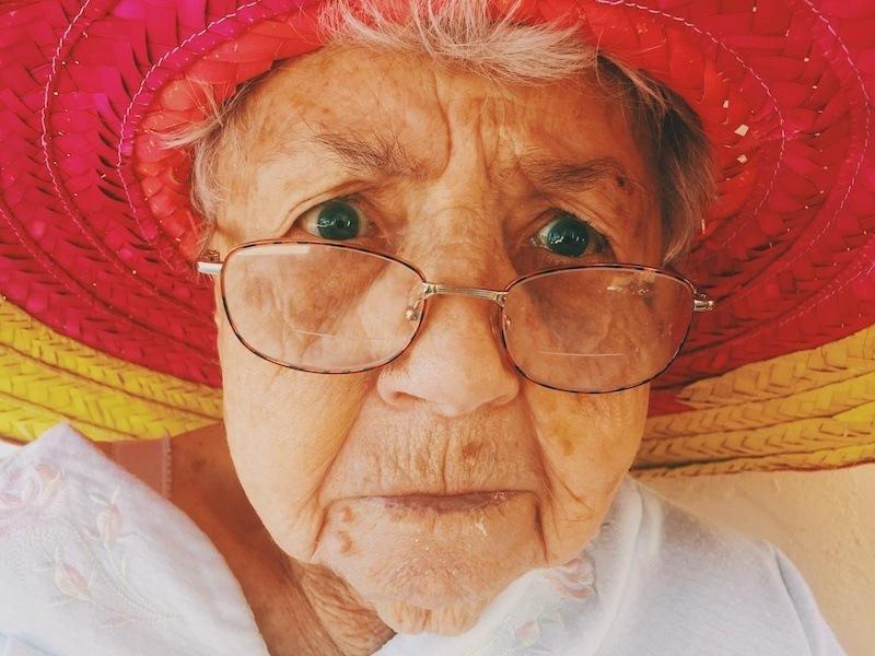 Alte Dame mit einem roten Sommerhut