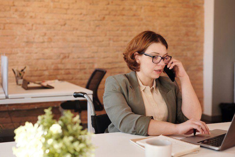 Bild: Frau am Laptop und mit Telefon in der Hand