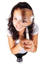 Bild: junge Frau lächelnd mit Lupe in der Hand